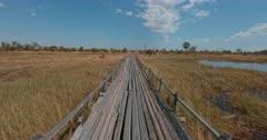 A tracking shot over a wooden bush bridge.
