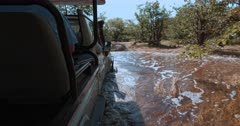 A tracking shot of a safari vehicle driving driving through deep water on flooded bush roads and getting stuck.
