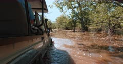 A tracking shot of a safari vehicle driving driving through deep water on flooded bush roads