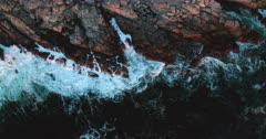 An aerial shot of waves crashing on the rocks.