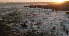 An aerial shot of the waves breaking on the rocks at sunrise.