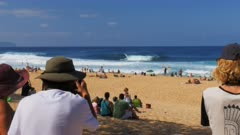 spectators and photographers watch the wave riders at the famous pipeline on the north shore of oahu