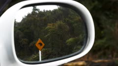 zoom in shot of a kiwi road sign reflected in a car mirror in new zealand