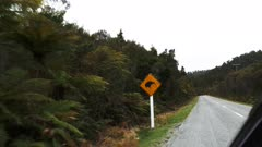 a car drives past a kiwi road sign in new zealand