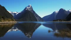 mitre peak reflected in the calm waters of new zealand's milford sound