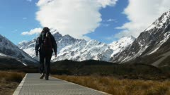 a hiker walks the trail in hooker valley with mt cook in the background