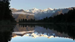 late afternoon panning shot of mt cook reflected in the waters of lake matheson in new zealand