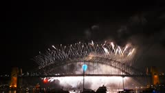 fire works begin to shower from the sydney harbour bridge on new years eve 2014- filmed in 4K