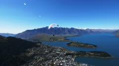 a paraglider takes off from skyline in queenstown, new zealand