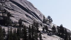 a zoom in shot of  pine trees on the face of polly dome at lake tenaya near tuolumne meadows