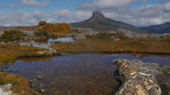 a zoom in shot of a large lichen covered rock in a high mountain tarn in tasmania's cradle mountain national park with barn bluff in the background