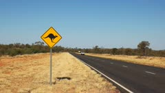 a van drives past a kangaroo road sign in outback australia