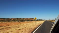 a car drives past a kangaroo road sign in outback australia