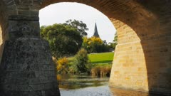 close up view of the historic old stone bridge and the spire of st john's catholic church framed by the arches of australia's oldest bridge in use