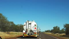 a car passes a road train in the northern territory of australia. a road train is a prime mover truck with three or four trailers.