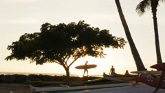 slow motion shot of the silhouette of a surfer carrying a long board at sunset in waikiki, hawaii