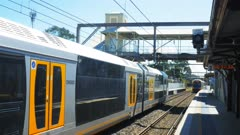 a commuter train passes another train waiting at a station in nsw australia