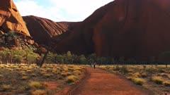 a close up of uluru/ayers rock and the mutijulu waterhole trail