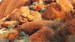 a vertical panning shot of boulders at the base of uluru