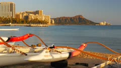 close up shot of outrigger canoes with waikiki beach and diamond head in the background