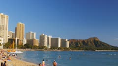a wide angle panning shot of waikiki beach with diamond head in the distance
