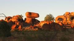 a close up of the devil's marbles in australia's northern territory at sunset