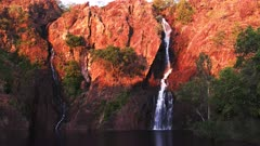 the setting sun turns the cliffs at wangi waterfalls in litchfield national park a brilliant red
