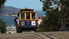 a san francisco cable car comes into view with a distant alcatraz island the background
