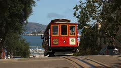 a red cable car with a distant alcatraz island in san francisco, california