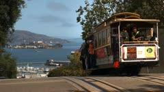 a san francisco cable car drives downhill towards a distant alcatraz island