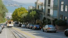 a cable car comes towards the viewer with a distant alcatraz island in san francisco, california