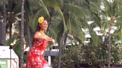 close up of an attractive female hawaiian hula dancer in a red dress performing at waikiki