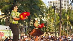 a male and female hula dancer with uliuli perform at waikiki beach, hawaii