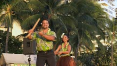 two hula dancers perform at waikiki with puili, a piece of dried bamboo approximately two feet long that has been split into strips down most of the length