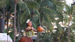a male and female hula dancer perform with gourds at waikiki