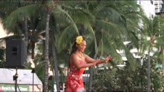 a slow motion clip of a female hula dancer in a red dress performing at waikiki