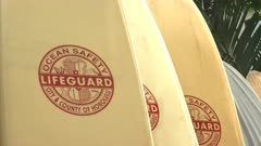 a panning shot of a number of lifeguard rescue surfboards at waikiki, hawaii