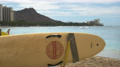 a lifeguard rescue surfboard at waikiki, hawaii with diamond head in the distance