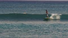 a young boy rides a longboard at waikiki beach, hawaii