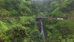 traffic slows at a narrow bridge above a  waterfall on maui's famous road to hana