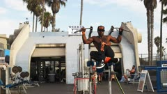 a bodybuilder worksout and displays his abdominal muscles and core strength at muscle beach in venice, california