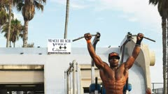 close up of a bodybuilder performing slow controlled pullups while exercising at venice beach, los angeles.