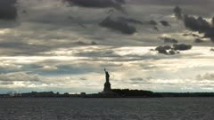 long view of storm clouds and a silhouetted statue of liberty in new york