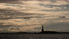 time lapse of storm clouds and a silhouetted statue of liberty in new york