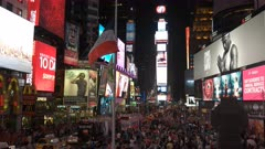 wide view of traffic and crowds at the electric times square in new york at night