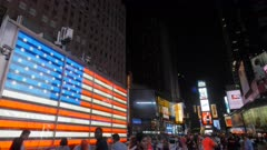 panning shot of the large neon us flag at times square in new york