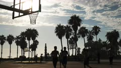 a basketball player slam dunks basketball at venice beach in los angeles