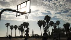 backlit shot of athletes playing street basketball at venice beach in los angeles