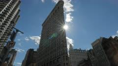 the sun shines behind the flatiron building in manhatten, new york