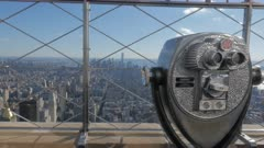 binoculars and the view of lower manhatten from the empire state building in new york